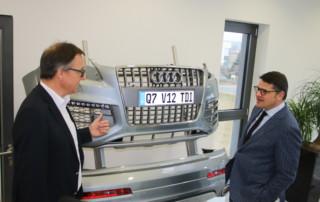 Stephan Kegelmann, Geschäftsführer Kegelmann Technik GmbH, im Gespräch mit Wissenschaftsminister Boris Rhein am Prototypen eines Stoßfängers